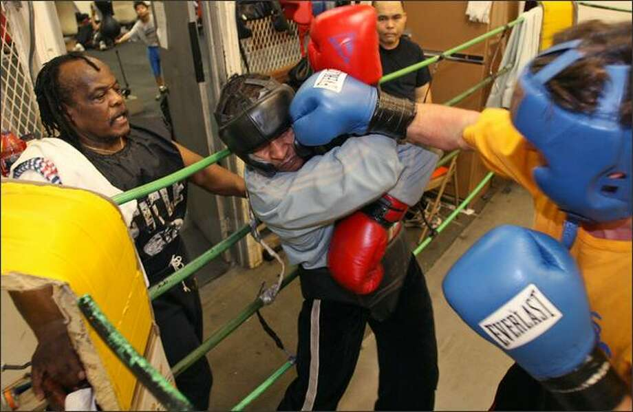 Willi Briscoeray, left, supervises boxers Jumanne Moore, center, and Zsolt Dornay, right, as they spar at Bumblebee Boxing Club in Seattle. The boxers are governed by two posters in the club: one with the house rules, the other a quote from Martin Luther King Jr. Photo: Mike Urban/Seattle Post-Intelligencer