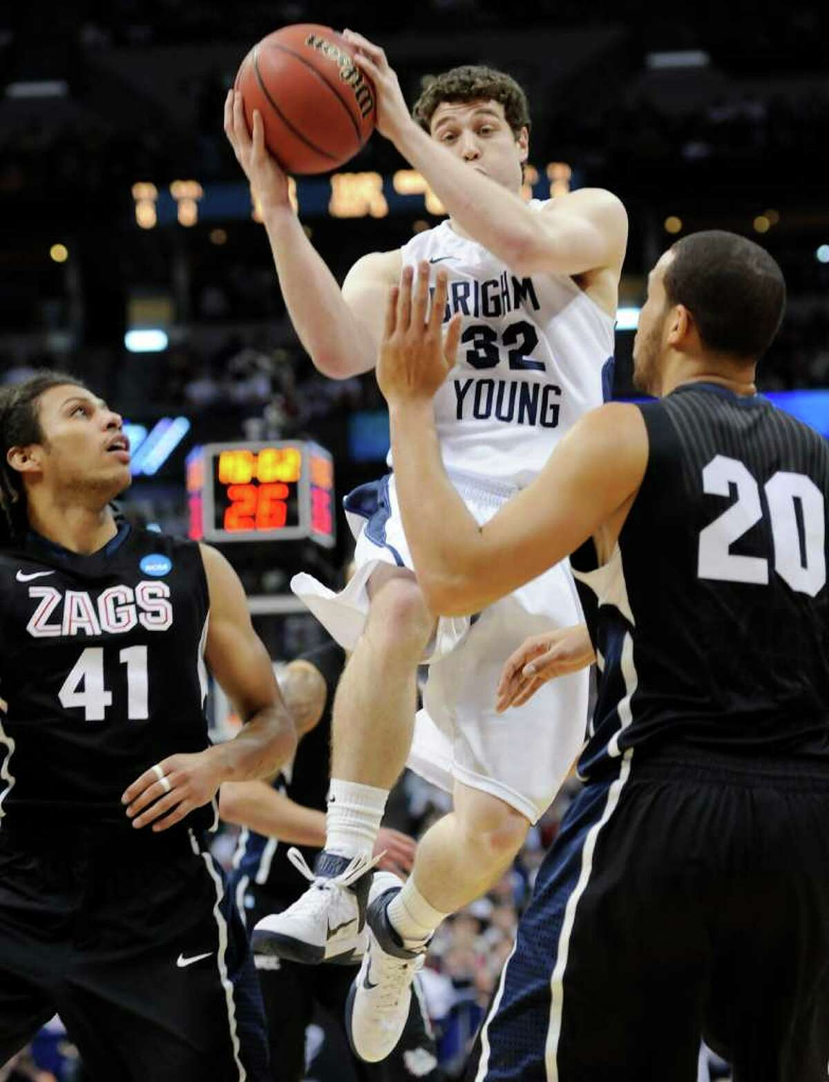 BYU guard Jimmer Fredette, a member of the Times Union Mount Rushmore of men's basketball, goes up for a shot against Gonzaga guard Steven Gray (41) and Gonzaga forward Elias Harris (20) in the first half of a Southeast regional third-round NCAA Tournament game, Saturday, March 19, 2011, in Denver. (AP Photo/Jack Dempsey)