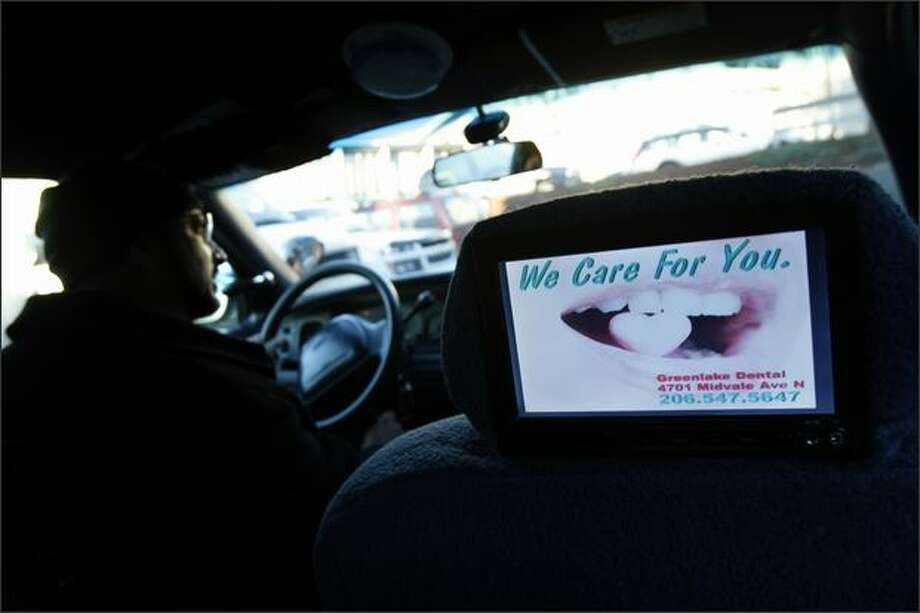 Mohd Ejaz Khan is one of 10 Orange Cab owners who recently had digital screens installed on the back of the head rests in his vehicle. The screens, which are part of a pilot project, display news headlines and advertisements to passengers. Photo: Andy Rogers/Seattle Post-Intelligencer