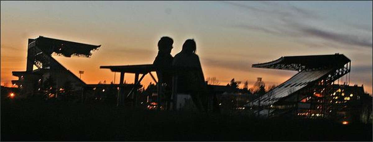 Students Alex Kummerow of the Seattle Art Institute and Sarah Overland of Seattle Central Community College enjoy the sunset behind Husky Stadium on Thursday from the Washington Park Arboretum.