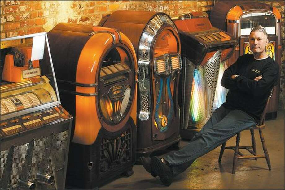 Jukebox collector and Luna Park Cafe owner John Bennett poses with some of his cherished machines from the 1940s and '50s at his Jukebox City showroom in Georgetown. Photo: Mike Urban/Seattle Post-Intelligencer