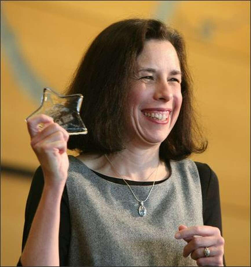Mary Erickson happily shows the award she received Sunday as Outstanding Mentor of the Year at the Guiding Lights Weekend at Seattle Center. Erickson has mentored a woman, now a UW student, for three years. Guiding Lights Network is seeking more mentors for waiting children. Photo: Paul Joseph Brown/Seattle Post-Intelligencer