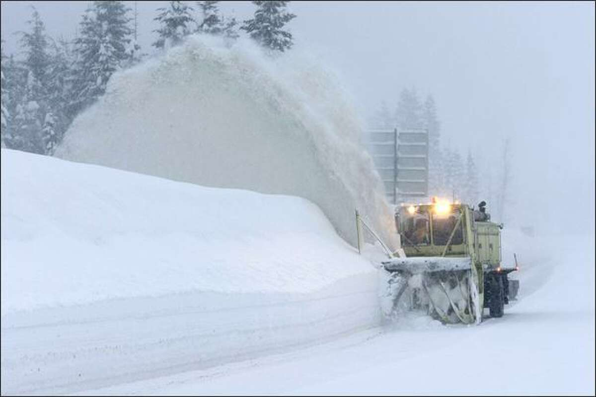 A Washington State Dept. of Transportation snow blower clears the right shoulder of a closed portion of eastbound I-90 near the summit of Snoqualmie Pass Tuesday.