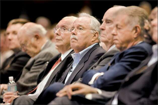 "Costco Chief Executive Jim Sinegal, center, told shareholders Tuesday at the company's annual meeting that the company is not ""particularly happy"" with a court ruling on the state's liquor control laws. Separately, he announced that Costco plans to nearly double in size to 1,025 warehouses. Photo: Grant M. Haller/Seattle Post-Intelligencer"
