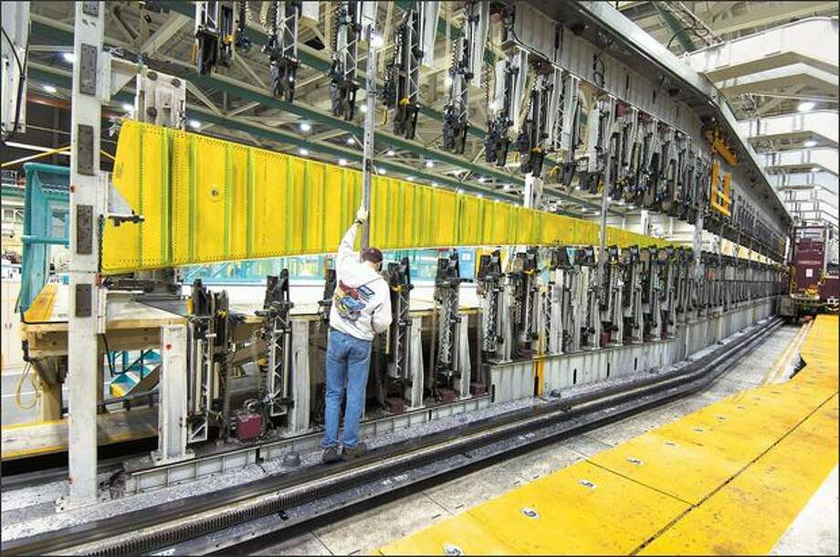 Boeing mechanics in Everett load a 97-foot-long wing spar Thursday into this machine that automatically drills, measures and installs more than 5,000 fasteners. Photo: / The Boeing Company