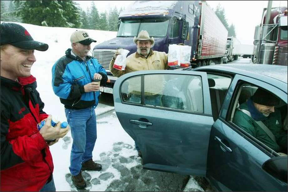 Chuck Rose, at right in car, and Lisa Parkins felt sorry for truckers stuck after Snoqualmie Pass was closed for avalanche control. Truckers themselves, they bought breakfasts and coffee from McDonald's and delivered them to truckers, from left, Brian Kavanaugh, Mark Crim and Joe Peak. Photo: PAUL JOSEPH BROWN/P-I PHOTO