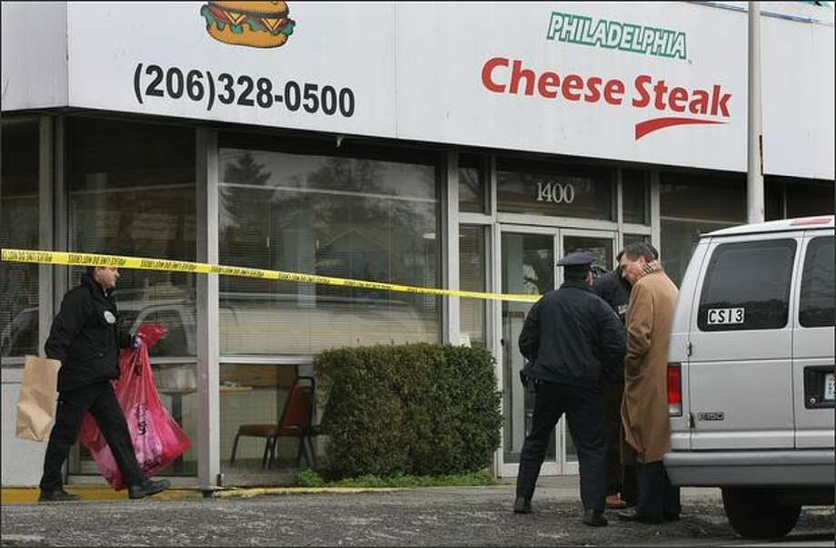 An officer talks with Chief Gil Kerlikowske, right, after a shooting Wednesday at the Philadelphia Cheese Steak restaurant in the Central District. One victim later died. Photo: Dan DeLong/Seattle Post-Intelligencer