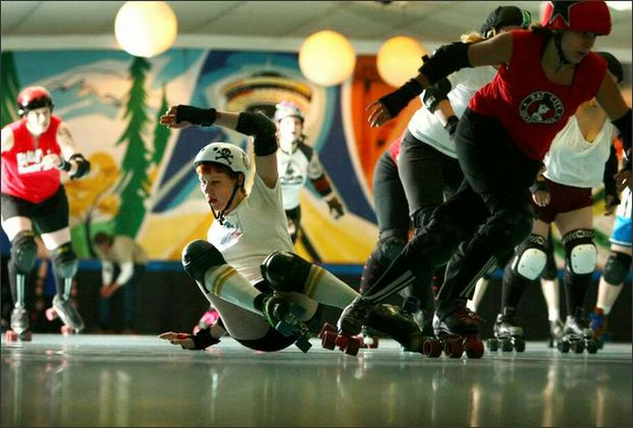 """Sandra Darling-Roberts, aka mommacherry, gets knocked down at a practice session Tuesday in Bellevue. The blocker for Rat City's Derby Liberation Front team likes roller derby because """"you get to be bad-ass."""" Photo: Joshua Trujillo/Seattle Post-Intelligencer"""
