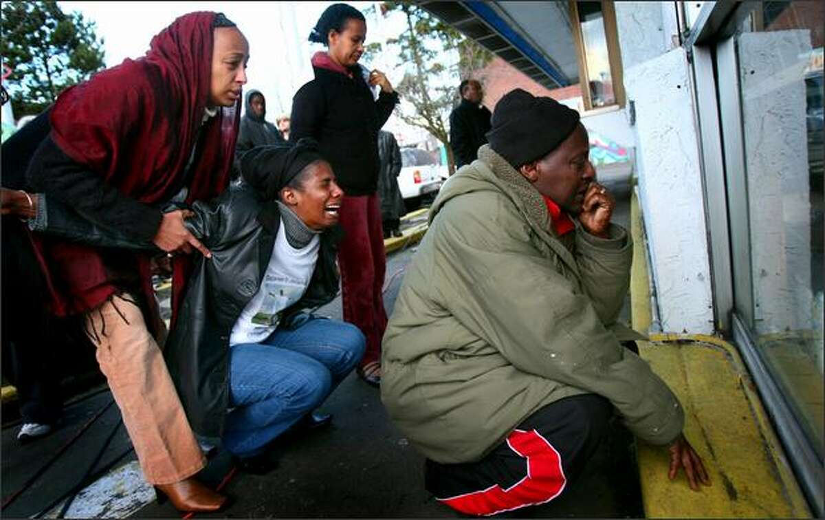 Godana Jatani, right, and Mulunesh Nora, crouching, react to the sight of a pool of dried blood at the Philadelphia Cheese Steak restaurant during a memorial.