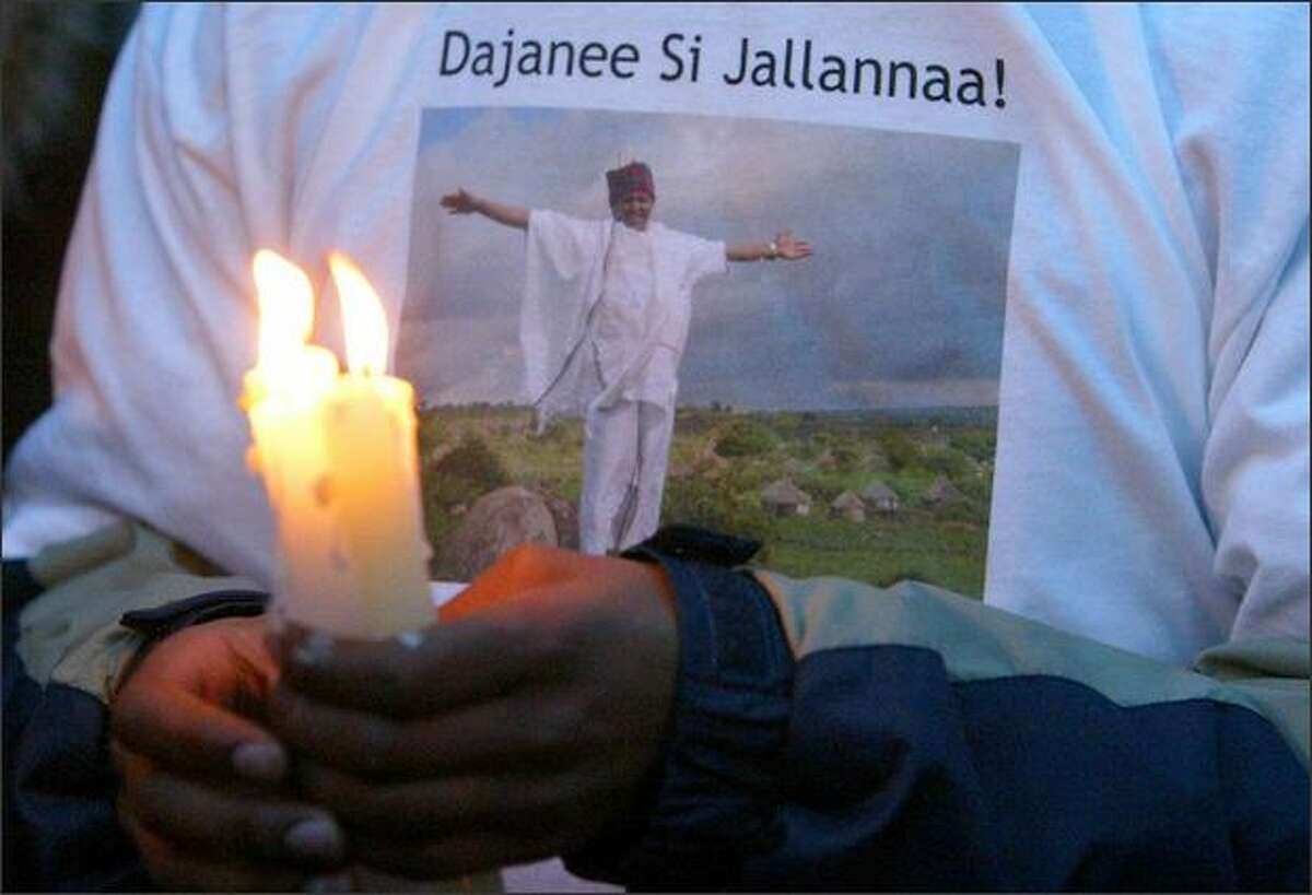 A family member holds candles during a memorial for Degene Barecha, who was shot Wednesday in his Central District restaurant.