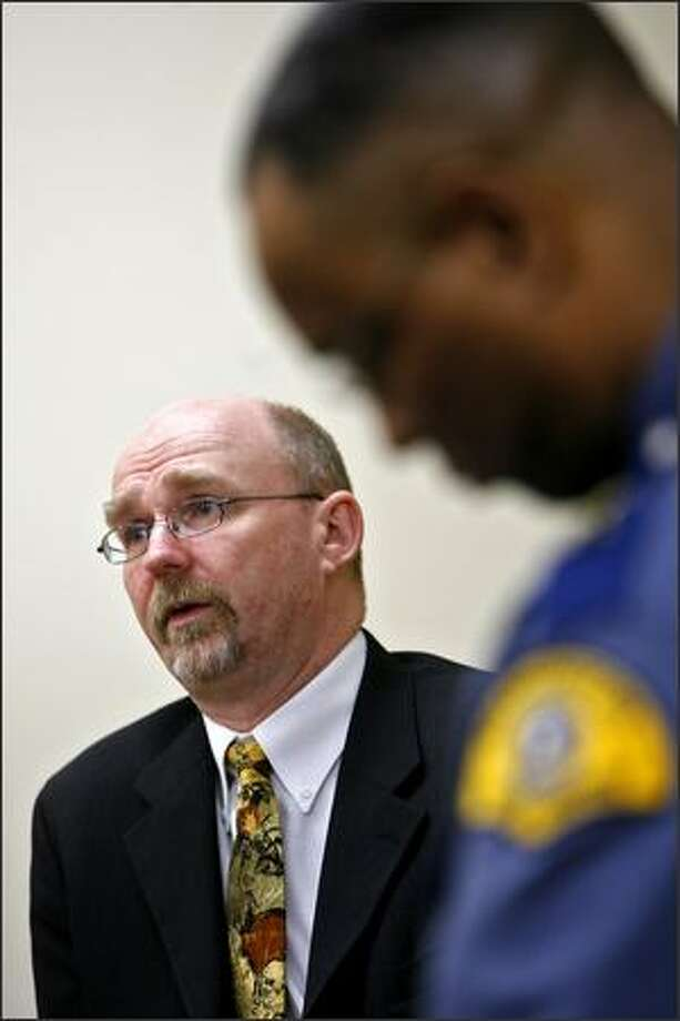 Barry Logan talks to the media Thursday about his crime lab resignation. At right is State Patrol Chief John Batiste. Photo: Mike Urban/Seattle Post-Intelligencer