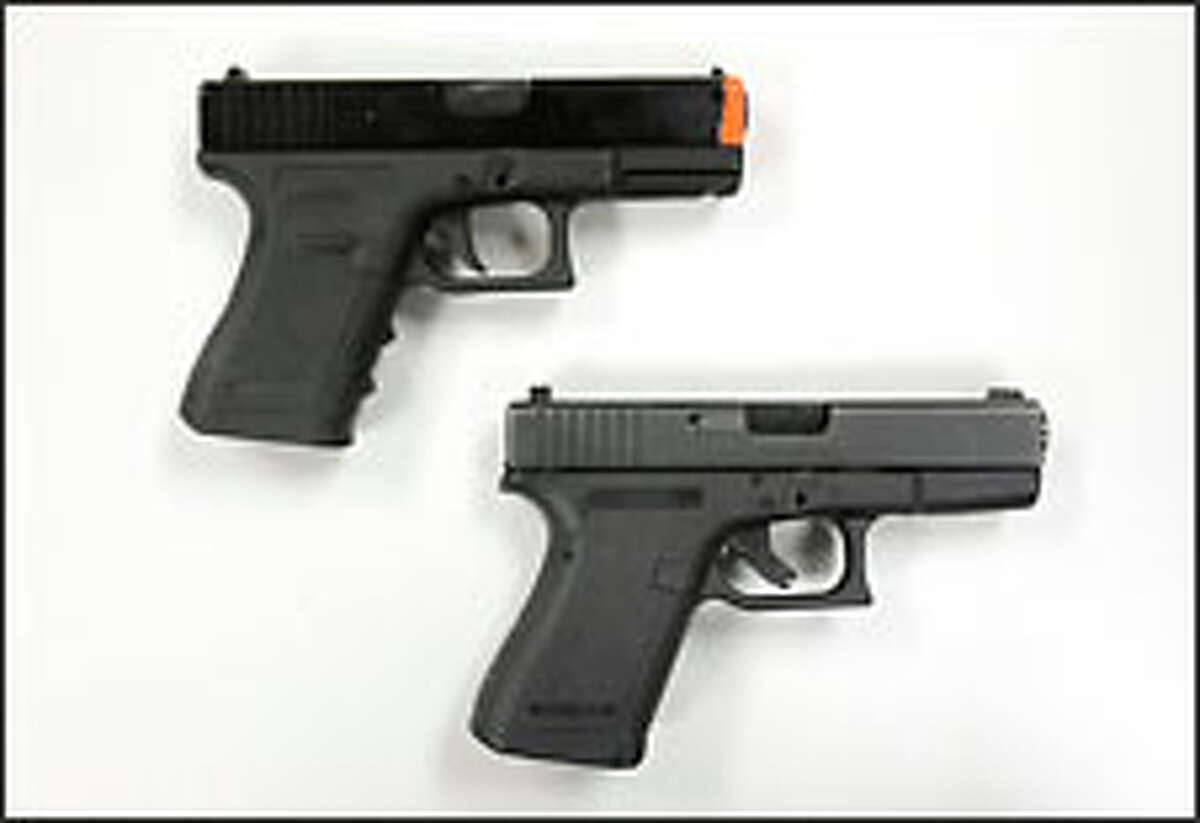 Top: Airsoft Glock BB gun used for police training.Bottom: A Seattle Police Department-issued Glock pistol.