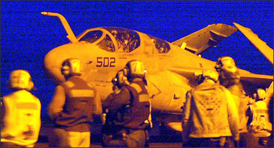 "Cast in a yellow light from the tower, an EA-6B Prowler from squadron VAQ-139 ""Cougars"" passes a crowd of observers on the flight deck, heading to take part in the first wave of the ""shock and wave"" assault on Baghdad. Photo: Grant M. Haller, Seattle Post-Intelligencer"