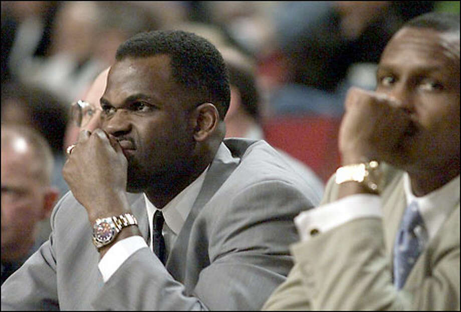 Coach Nate McMillan and associate head coach Dwane Casey are grim as they watch a 2002 Playoffs game wind down, putting the Spurs ahead 2-1 in the best-of-five series. Photo: Paul Kitagaki Jr., Seattle Post-Intelligencer