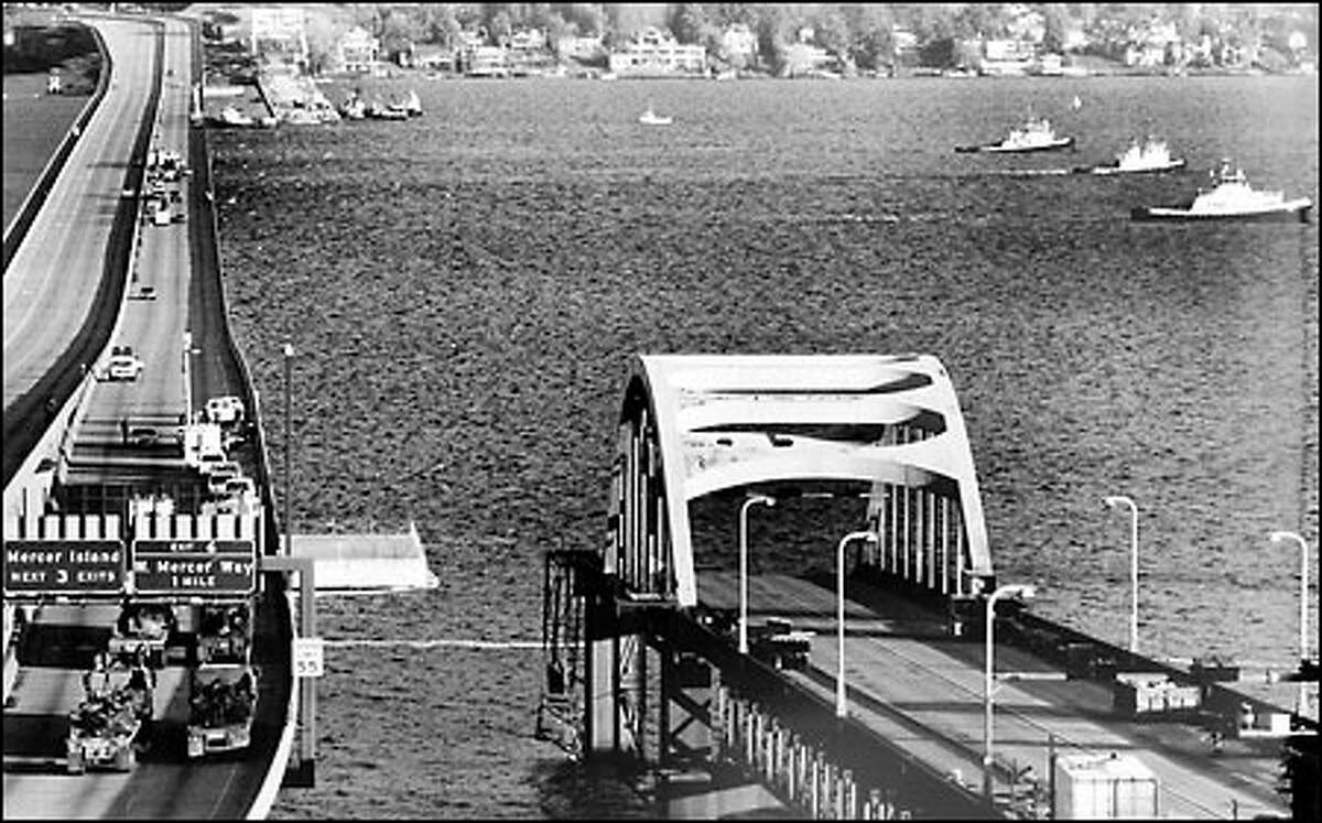 Link to Eastside collapses, 1990: One day after the sinking of the old Interstate 90 floating bridge, tugs pull on the new bridge, keeping it from breaking up as crews work to set new anchors. Storms threatened the stability of the new bridge, its supporting cables damages with the old span went under because of waterlogged pontoons.