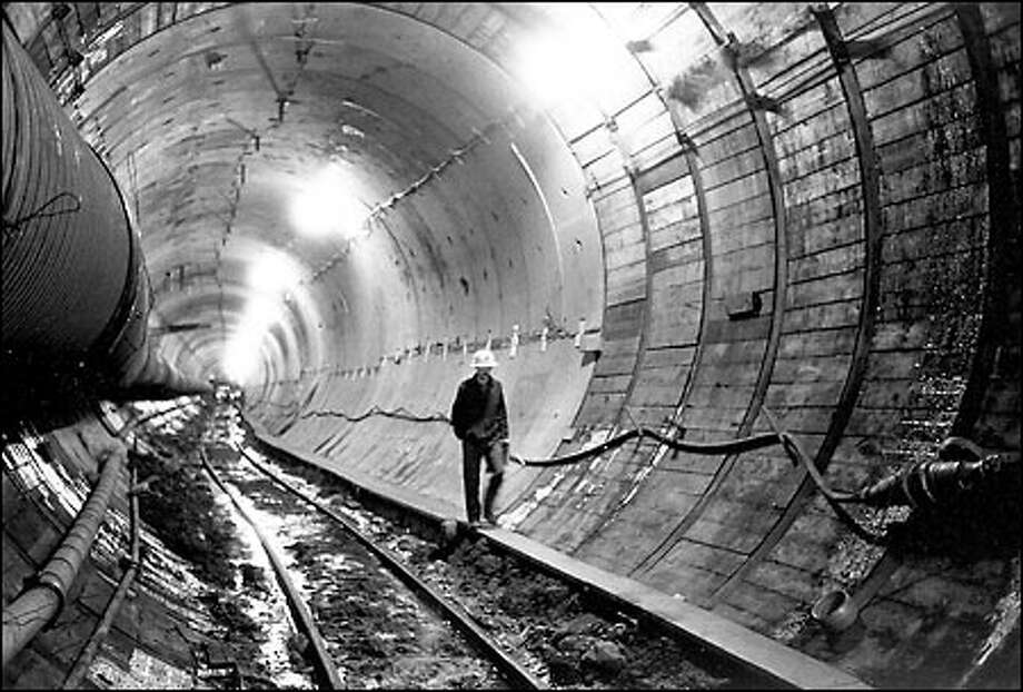 Construction of Metro bus tunnel under Third Avenue, 1988: Alphonse Pieper, a Metro construction inspector, walks along Seattle's bus tunnel during construction. A monument to urban design, the $459 million tunnel took four years to build and opened Sept. 15, 1990. Up to 18,000 bus riders  per hour can use the tunnel. Photo: Cary Tolman, Seattle Post-Intelligencer