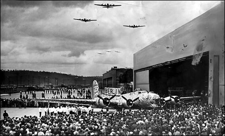 "Salute from the skies, 1945: A ceremony at The Boeing Co.'s Plant 2 commemorates delivery of the last Seattle-built B-17 ""Flying Fortress"" in April 1945. The B-17 on the ground is decorated with cardboard bombs, representing a raid on Germany. In the air, three B-17s are followed by three B-29 Superfortresses. Photo: Seattle Post-Intelligencer"