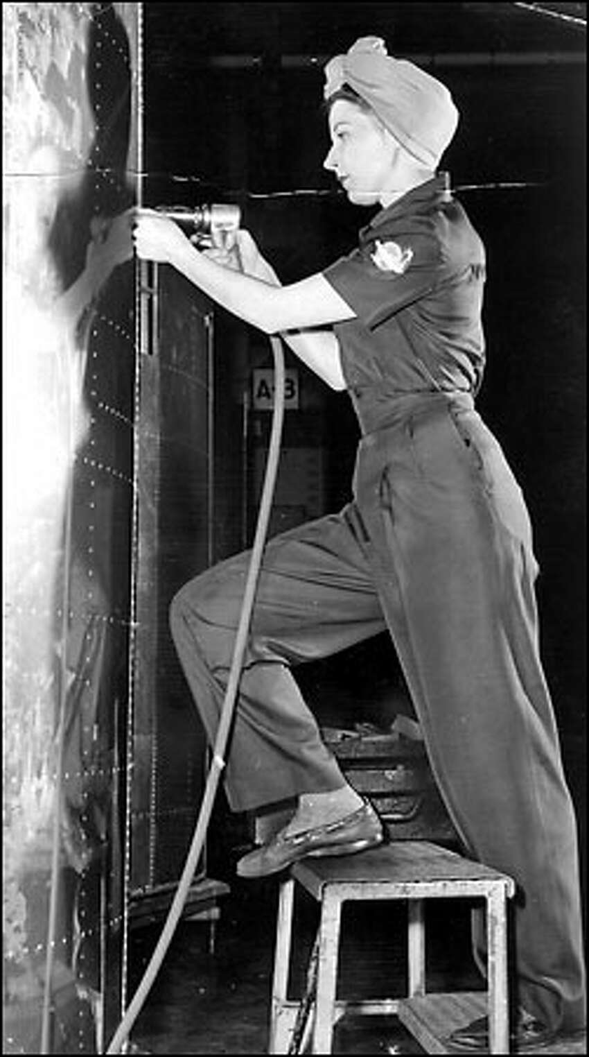 Rosie the Riveter, 1943: Elaine Tosch does her riveting clad in a fashionable Flying Fortress uniform by Miss King. Thousands of women joined the Boeing production line during World War II as airplane output shifted into high gear.