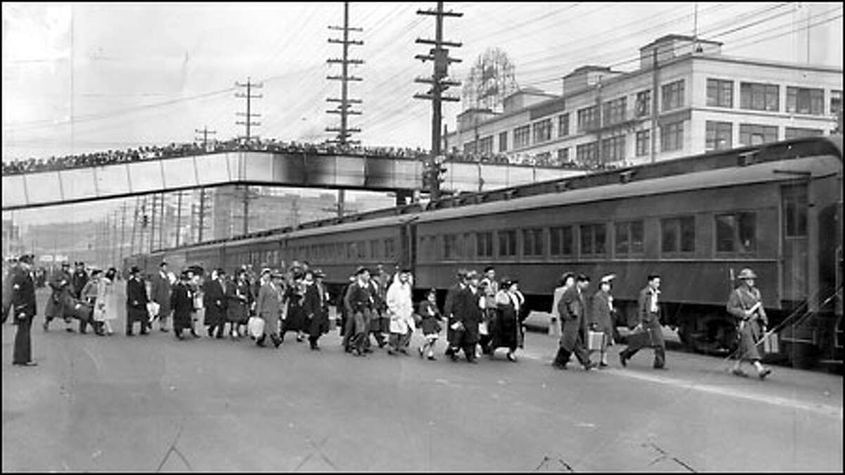 Internment of Japanese Americans, 1942: In the first evacuation of local Japanese Americans to internment camps in California and Idaho, 225 residents of Bainbridge Island are rounded up, delivered by ferry to Colman Dock and escorted onto trains by Army troops Mar. 30, 1942. A crowd watches from the Marion Street overpass. Eventually, 12,892 people of Japanese ancestry from Washington state were incarcerated.