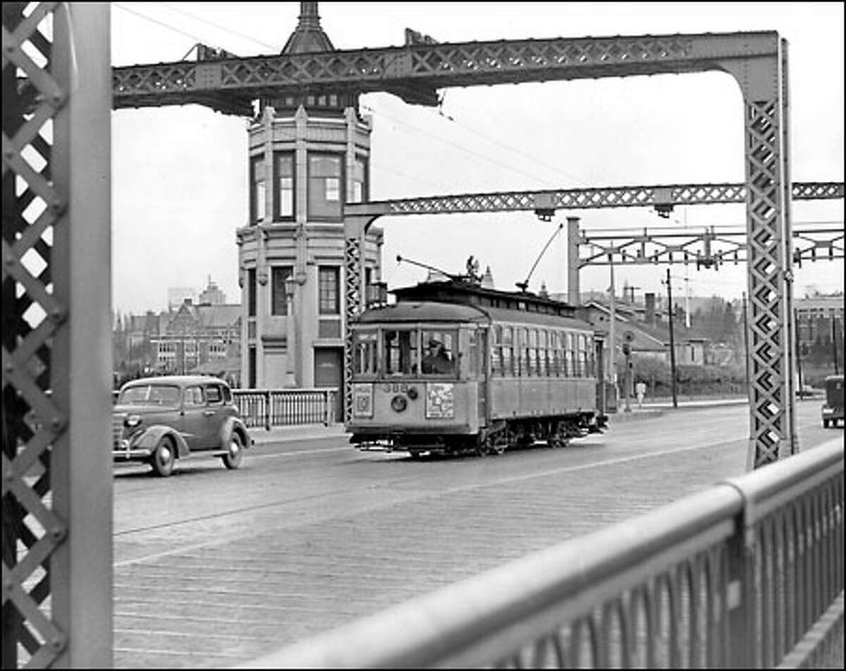 Montlake streetcars soon to be a memory: The Montlake bridge tender would not see this familiar sight much longer after 1940, the approximate year this photo was taken. Streetcars that carried thousands of football fans to Husky Stadium over this span disappeared, as they did soon afterward from many of Seattle's streets.