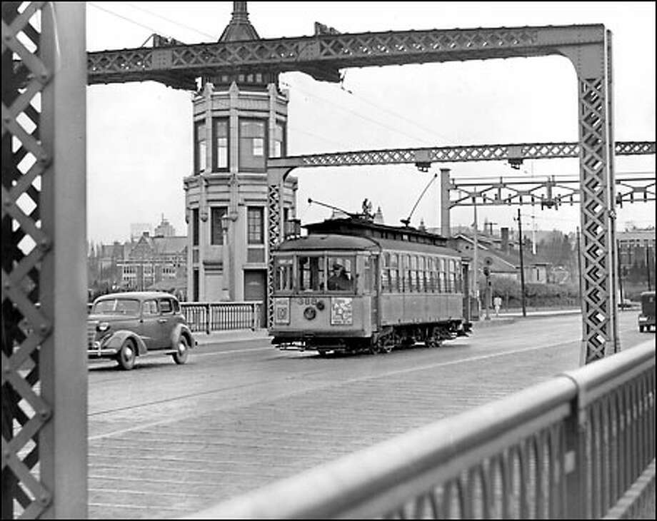 Montlake streetcars soon to be a memory: The Montlake bridge tender would not see this familiar sight much longer after 1940, the approximate year this photo was taken. Streetcars that carried thousands of football fans to Husky Stadium over this span disappeared, as they did soon afterward from many of Seattle's streets. Photo: Seattle Post-Intelligencer
