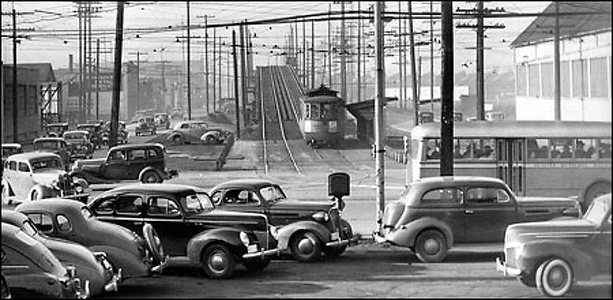Traffic congestion, 1940: On a normal day of traffic in Seattle, trolleys, buses and cars converge in the industrial area at the intersection of Fourth Avenue South and South Spokane Street. By 1944, the Spokane Street Viaduct was completed, and it diverted some of the regular traffic, making Fourth an easier route into downtown.
