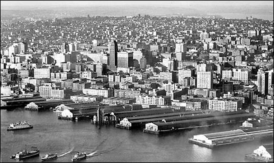 Seattle skyline, 1939: Along Seattle's waterfront, finger piers, side by side, extended into Elliott Bay for decades. Seattle's Colman Dock, near center in foreground, once held a well-known landmark, the clock tower. Photo: Seattle Post-Intelligencer