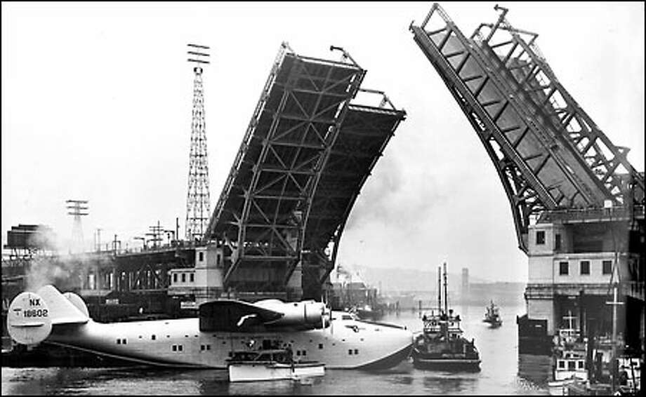 Boeing Clipper in tow, 1938: Towed by two tugboats, the second in a fleet of six Boeing Clipper airplanes leaves the factory's dry dock. In this picture, the huge plane is edged sideways through the Spokane Street Bridge. Because of the size of the plane, extreme care had to be taken under the bridge. It barely squeezed through. Photo: Seattle Post-Intelligencer