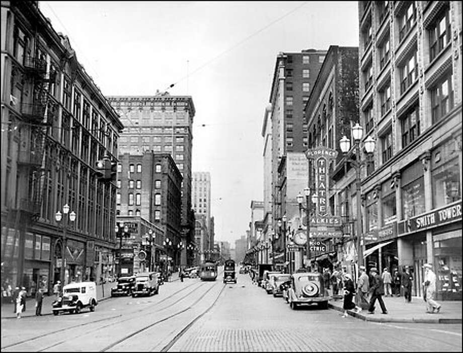 "Second Avenue, 1935: Daytime traffic in 1935 seems sparse except for streetcars and pedestrians near the familiar Smith Tower, in this view looking north along Second Avenue from Yesler Way. After dark, moviegoers could sit in the ""talkies"" all night, according to the street-level advertisements for the Florence Theatre. Photo: Seattle Post-Intelligencer"