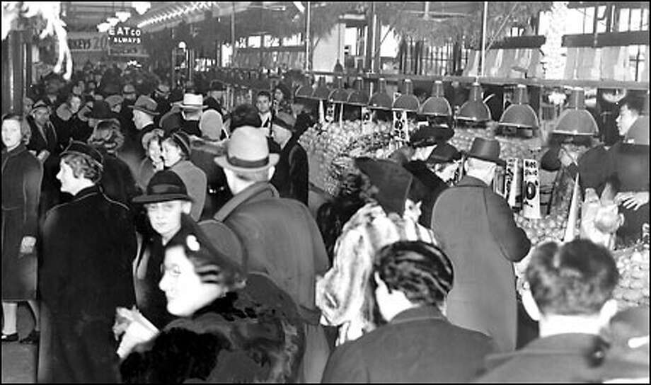 Christmas season, 1939: Swags of greenery decorate the food stalls as holiday shoppers in hats and overcoats crowd the Pike Place Market just before Christmas 1939. Stores reported booming business as shoppers scurried to take advantage of low mid-winter prices. All winter, local sports fans watched a team called the Seattle Seahawks – play hockey. The team ended the 1939-40 season with a losing record of 16-21-3. Photo: Seattle Post-Intelligencer