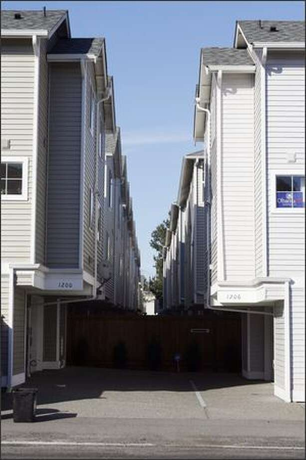"The driveway or ""auto court"" that bisects many townhouses is dreary and barren. Former city councilman and architect Peter Steinbrueck asks, ""Who wants to look into these narrow, dark, paved-over spaces?"" Photo: Gilbert W. Arias/Seattle Post-Intelligencer"