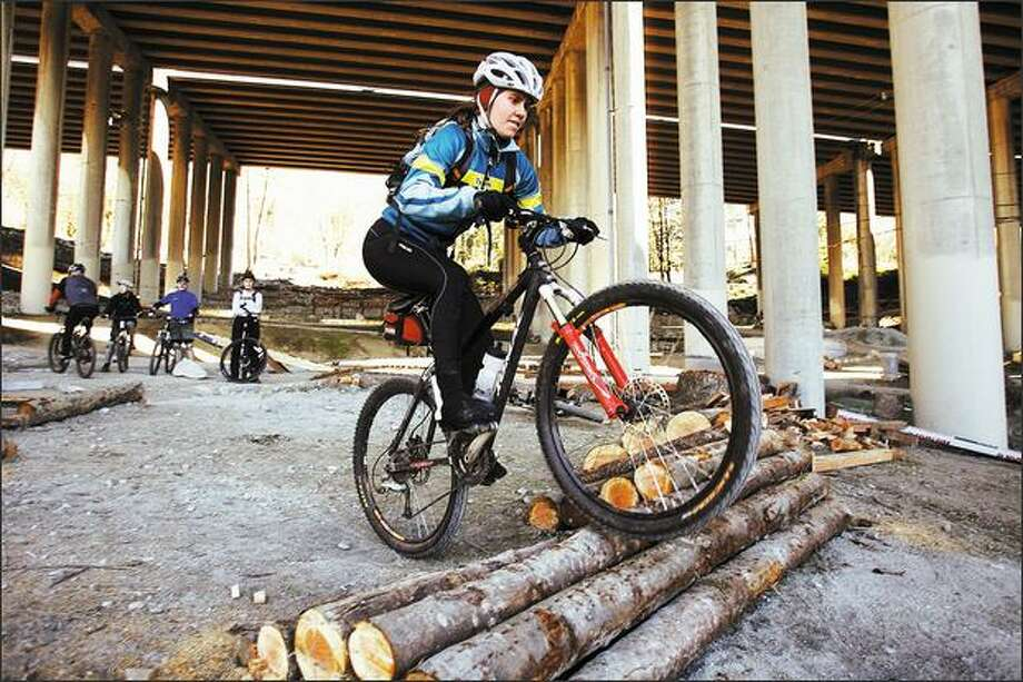 """Lori Williams sharpens her riding ability with a """"skills session"""" with a group from the Backcountry Bicycle Trails Club in a class at Colonnade Park under I-5. Photo: Mike Urban/Seattle Post-Intelligencer"""