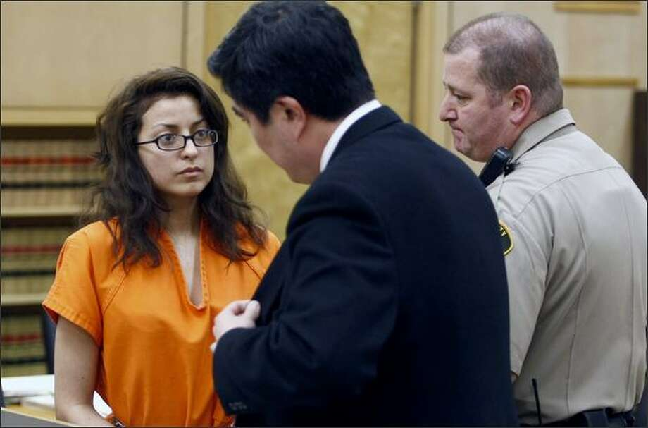 Army Spc. Ivette Gonzalez Davila, shown talking with her lawyer in Tacoma on Monday, is accused of killing a couple and pouring acid on the bodies. Photo: Andy Rogers/Seattle Post-Intelligencer
