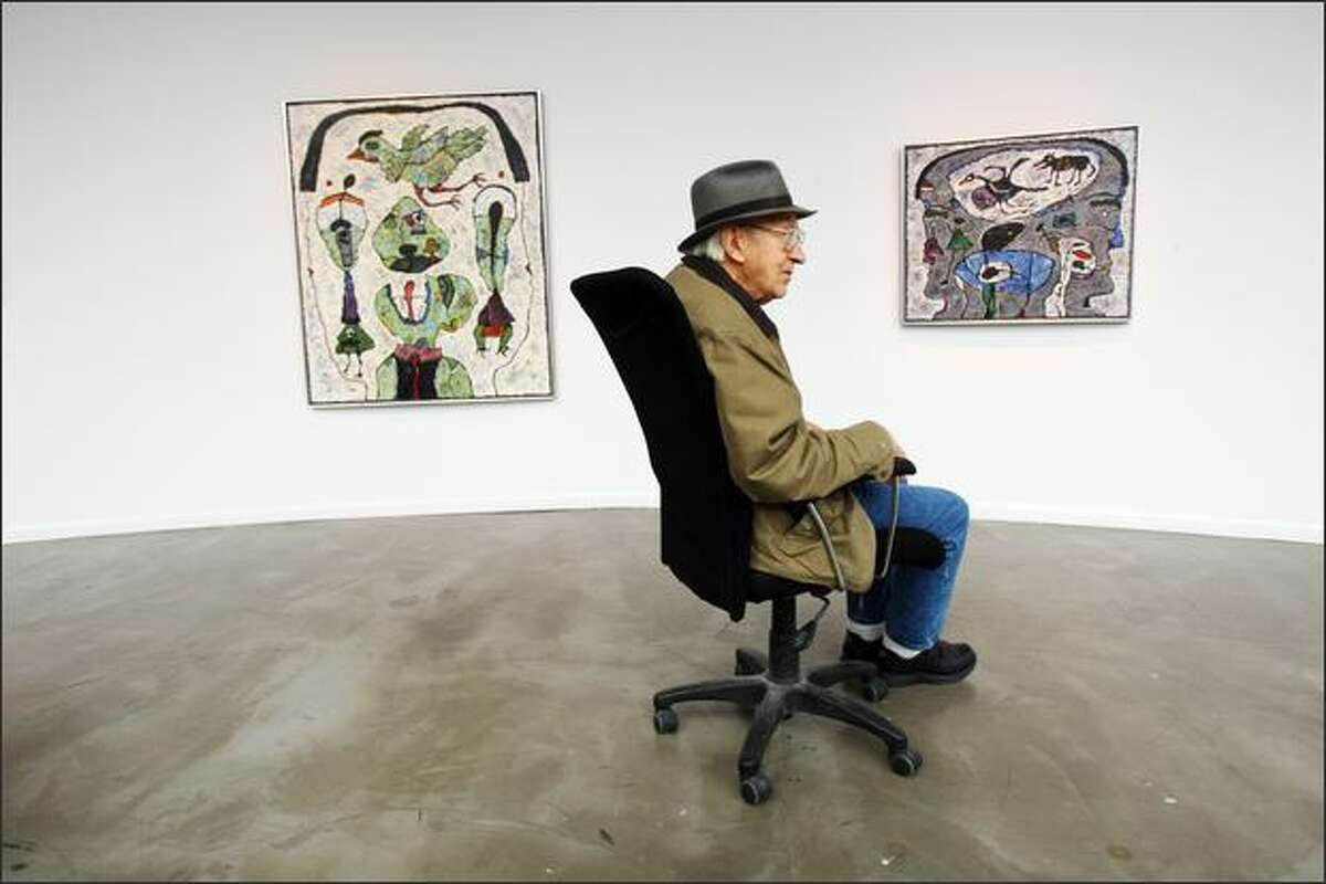 Alden Mason sits with two of his pieces at the Foster/White Gallery on Monday. Mason's work will be shown this month at Foster/White and at Greg Kucera Gallery.