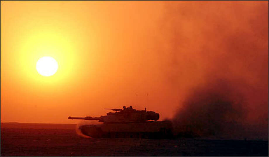 "An Abrams tank races through the Iraqi desert as the sun sets yesterday, the 10th day of the war. President Bush has warned of ""further sacrifice"" ahead in the face of unexpectedly fierce fighting. Photo: Bahram Mark Sobhani, San Antonio Express-News"