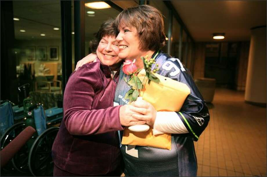 "Annamarie Ausnes, left, greets barista Sandie Andersen with a rose on Andersen's arrival at Virginia Mason Medical Center for the kidney transplant surgery Tuesday. All went fine. ""If you can save somebody's life, it's special,"" said Jeffrey Andersen, Sandie's husband. Photo: PAUL JOSEPH BROWN/P-I"