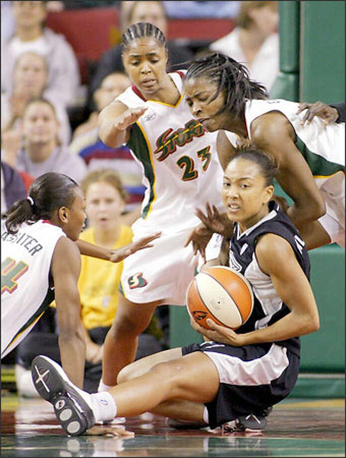 Amanda Lassiter, Rita Williams and Simone Edwards defend Tai Dillard. Photo: Associated Press