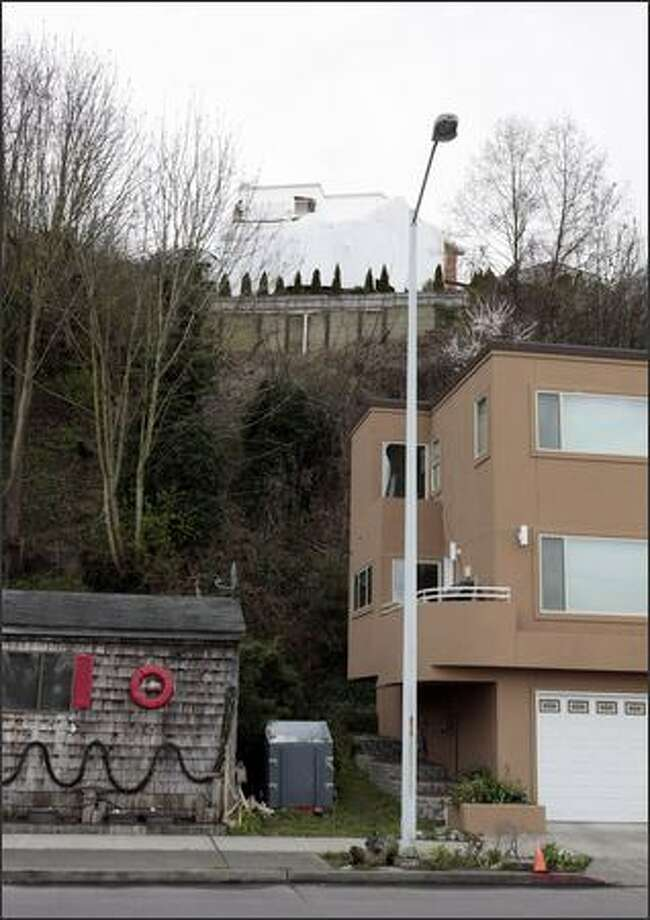 John Hendrickson, who lives in the house with the red ring on the wall, said he never knew there was a retaining wall above his house till the trees were cut down. Photo: Meryl Schenker/Seattle Post-Intelligencer