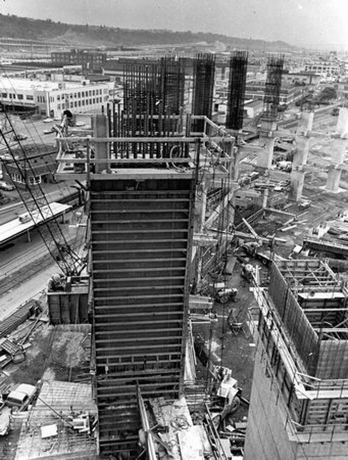 The June 1973 photo caption read: Half way up-workers on the ground are dwarfed in this view looking south along the row of pillars which will support the east end of the roof. Photo: P-I File / P-I File
