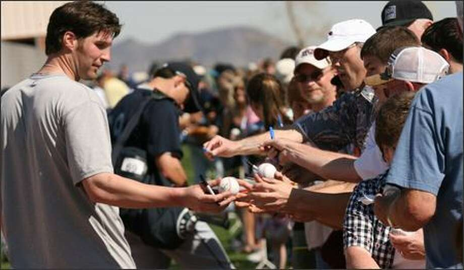 Richie Sexson hands an autographed ball back to a fan after Wednesday's workout. Photo: Grant M. Haller, Seattle Post-Intelligencer