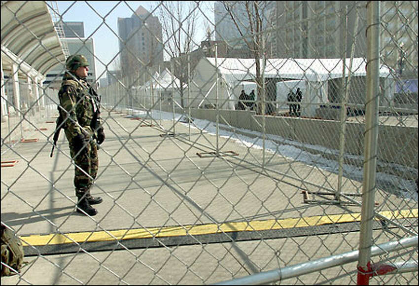 A solider stands guard outside the Main Press Center with an M-16 weapon.