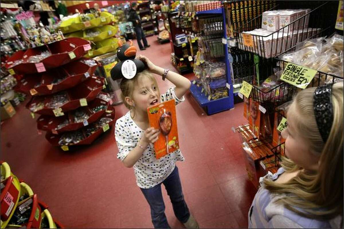 Kyra Waserekke, 8, left, pretends to lick an ear-on-a-stick Wednesday while teasing her sister, Miya Waserekke, 9, as they peruse the toys and other novelties sold at Archie McPhee, a Ballard landmark that might have to close its doors if a state toy ban passes.