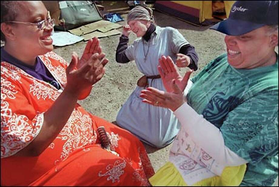 "Tent City residents celebrate after being led in prayer by benefactor Lynne Duchesne, right, who has donated time and food to help the camp. Angel Blake, left, said: ""Tent City is great. Nobody is going to get hurt; have all these big men to protect us."" Photo: Renee C. Byer, Seattle Post-Intelligencer"