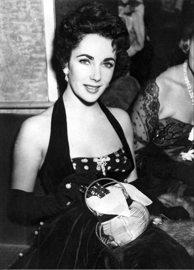 "American actress Elizabeth Taylor is shown at the premiere of ""The Lady with the Lamp"" at the Warner Theater in London, England, Sept. 22, 1951. (AP Photo)"