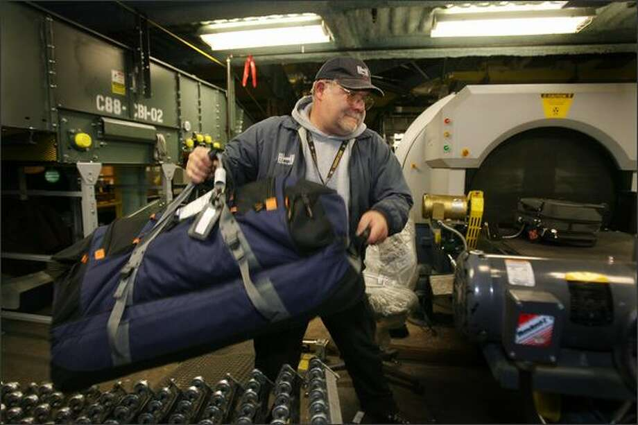 David Spence, lead bag runner, transfers luggage to the X-ray machine at Sea-Tac International Airport. In March, Spence, 51, lost a skycap job he'd had since 1997 at the Alaska Airlines curb. He now makes a bit more than minimum wage, but no tips. Photo: Dan DeLong/Seattle Post-Intelligencer