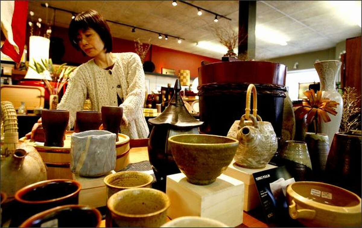 Naoko Nibu-Butler arranges a display at Kobo on Jackson Street. The store sells many fine-art items, including delicate, imported teapots.