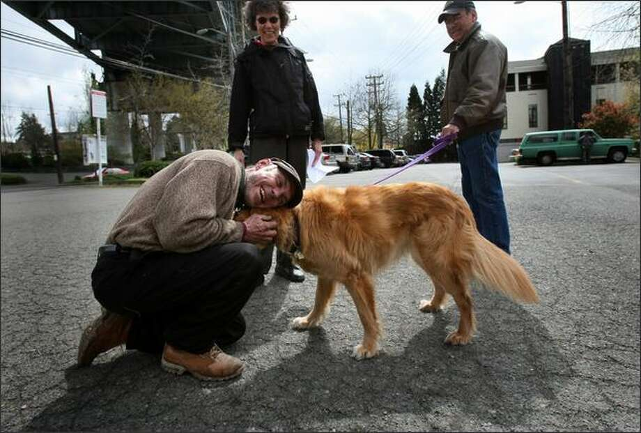 "David Csaky, aka ""Squirrelman,"" hugs everyone in a parking lot -- including neighborhood dog Max, leashed to owner Jim Nelson with Janet Yoder in back -- after news was delivered to Csaky that his eviction order was extended for 10 more days to move out of his elaborate treehouse. Photo: Joshua Trujillo/Seattle Post-Intelligencer"