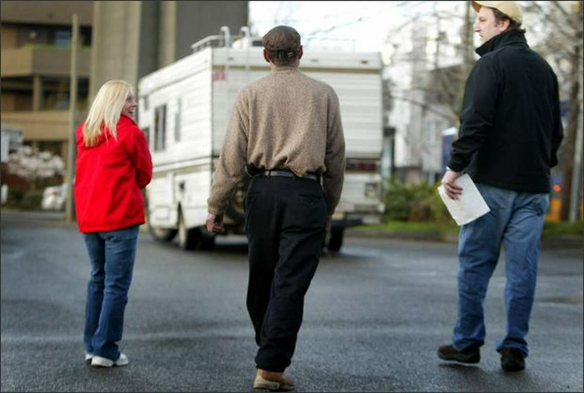 Amy and Timothy Custer walk with David Csaky, center, to his new home -- a used RV they sold to him for a special