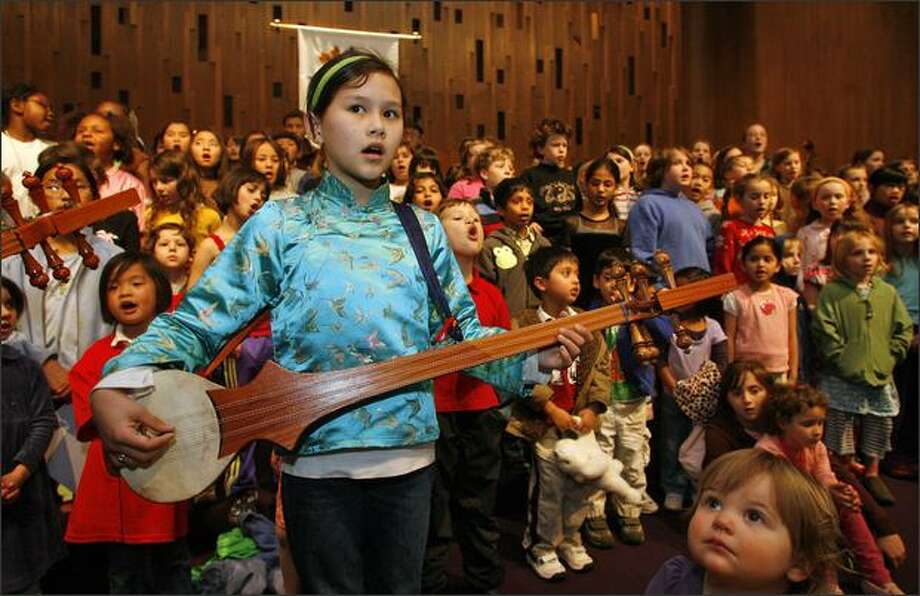 Tshedzom Tingklye, 10, of Seattle, plays the dramyen, a traditional Tibetan stringed instrument, as she and 1,800 other members of the Seeds of Compassion Choir, led by Mary K. McNeill, rehearse at Seattle Unity Church on Thursday. Photo: Mike Urban/Seattle Post-Intelligencer