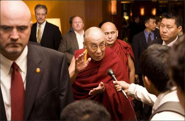 Flanked by security personnel, the Dalai Lama answers questions upon arriving at his hotel in Seattle on Thursday. Photo: / Associated Press